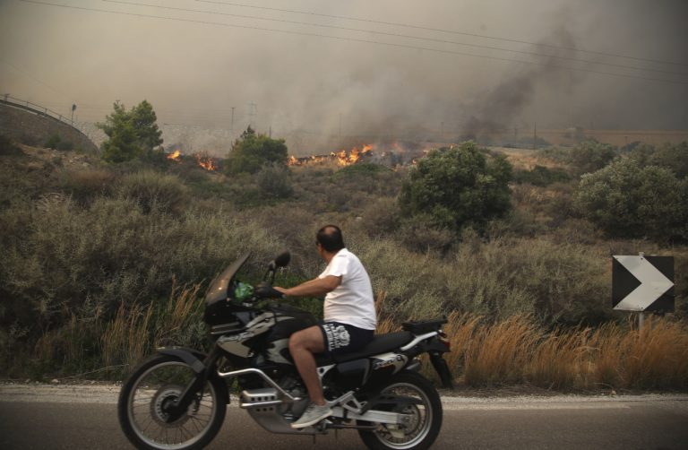 A motorcyclist looks at smoldering shrubbery on a road near Kineta west of Athens on Monday
