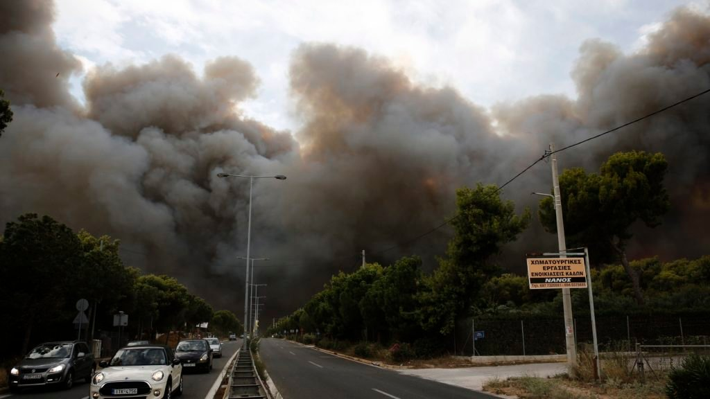 Smoke rise over an avenue during a forest fire in Neo Voutsa a northeast suburb of Athens Greece on Monday